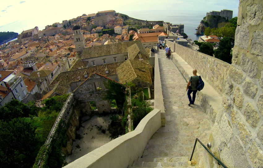 The view of the town from the top of the Wall of Dubrovnik in Croatia Dubrovnik, Croatia Vacations Wall Adult Ancient Architecture Building Exterior Built Structure Day Full Length High Angle View History Leisure Activity Lifestyles Men Nature One Person Outdoors Real People The Past Tour Tourism Travel Visit Walking The Traveler - 2018 EyeEm Awards