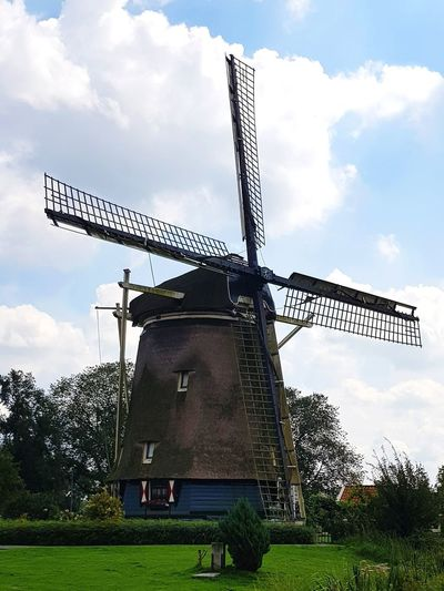 Traditional windmill on field against sky