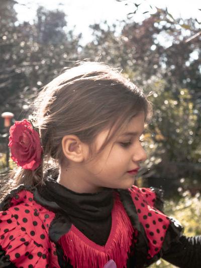 Cute girl wearing rose looking away at park