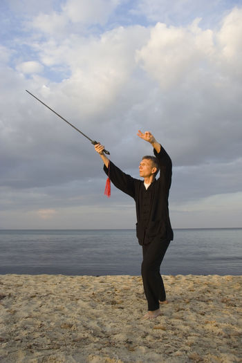 Young man practicing tai chi at beach against cloudy sky