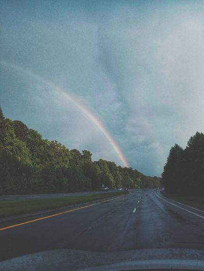 Rainbow over road against sky