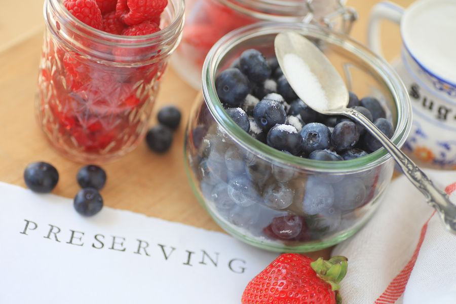 Fresh berries with preserving word and glass jars Blue Blueberries Close-up Color Dish Towel Fabric Food And Drink Fresh Fruit Glass Jars Natural Light No People Overhead Preserving Raspberries Red Spoon Still Life Strawberries Sugar Table Text Space Textures White Word