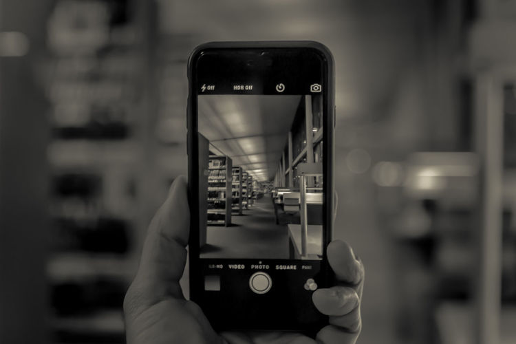 Cropped image of woman photographing through smart phone