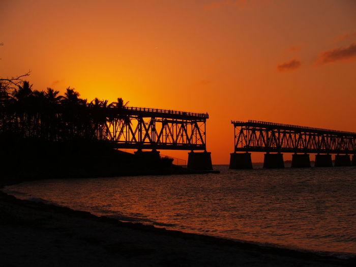 Silhouette Incomplete Bridge On Lake Against Orange Sky