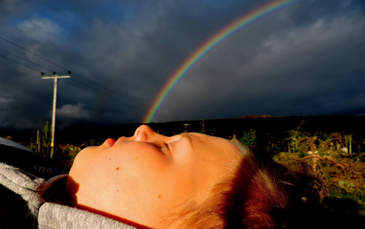 LOW ANGLE VIEW OF WOMAN LYING DOWN ON MULTI COLORED LAND