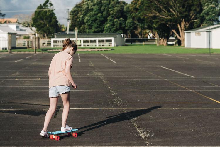 Full length of woman standing on skateboard