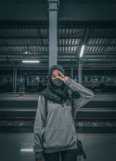 Full length of hijab woman standing at railroad station