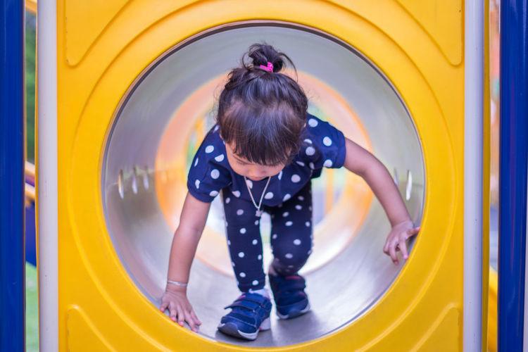 Full length of cute girl sliding in tube at playground