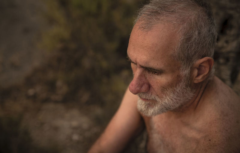 Close-up portrait of shirtless adult man