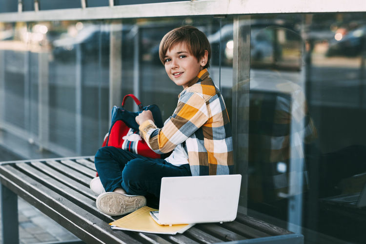 Portrait of smiling girl holding glass while sitting outdoors