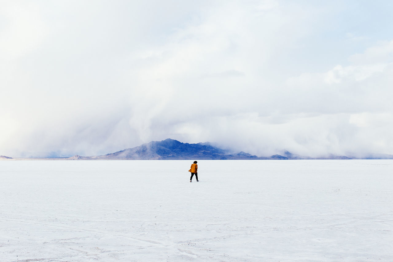 Distance shot of woman walking on snow covered landscape