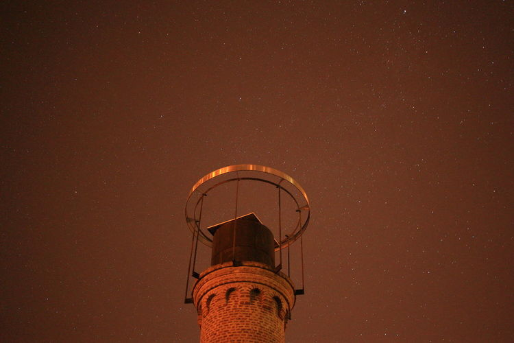 Low angle view of water tower against sky at night