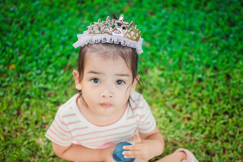 High angle portrait of cute girl wearing tiara while sitting on grassy field at park