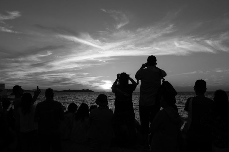 People at beach against sky