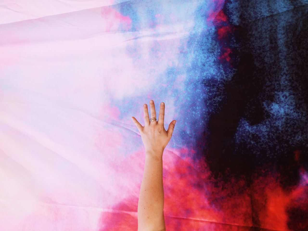 Cropped image of woman with hand raised against textile