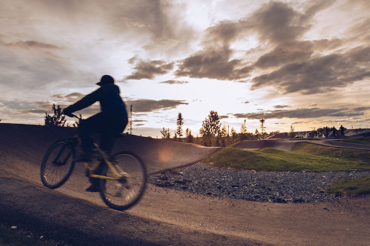 Man riding bicycle against sky during sunset