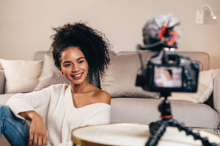Vlogger Blogger Smiling Indoors  Sitting Lifestyles Home Interior Emotion People Real People Looking DSLR Camera Content Influencer Social Media Recording Video Females Happiness Podcast Explaining  person Hairstyle Portrait
