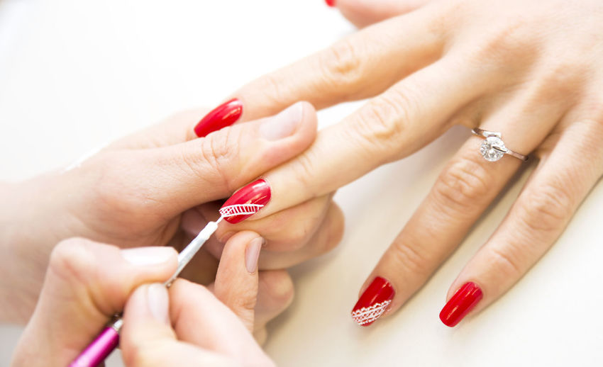 Cropped hand of woman applying nail polish to friend