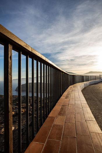 Empty footpath by railing against sky