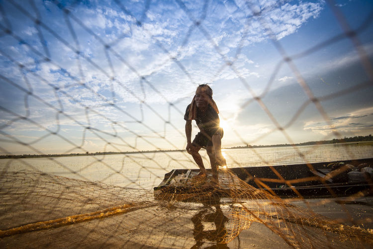 Fisherman holding fishing net at sea against sky