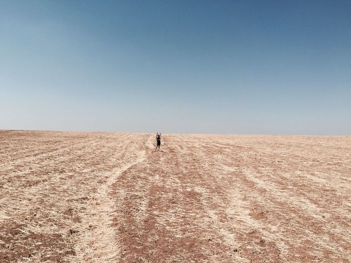 Mid Distance Of Woman Standing On Field Against Sky