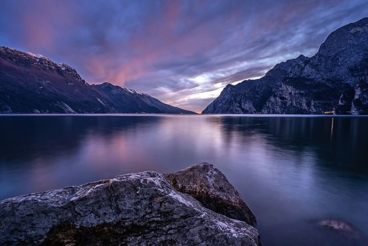 Scenic view of lake garda against sky during sunset