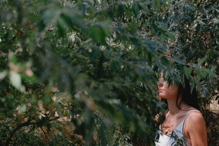 Side view of woman standing amidst plants
