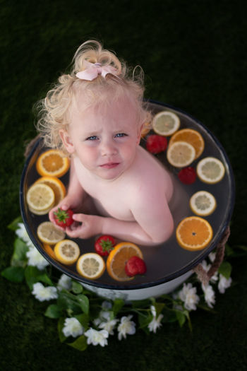 High angle portrait of cute girl sitting at bucket with fruit