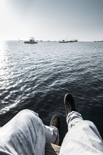 Low section of men sitting by sea against sky