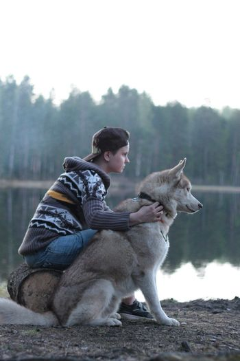 Side view of young woman sitting with siberian husky at lakeshore