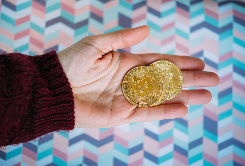 Hand holding bitcoins on colorful background E-commerce Bitcoin Blockchain Coins Cryptocurrency Hand Money Pay