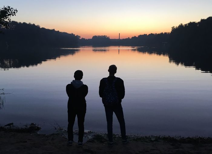 Silhouette men standing on lake against sky during sunset