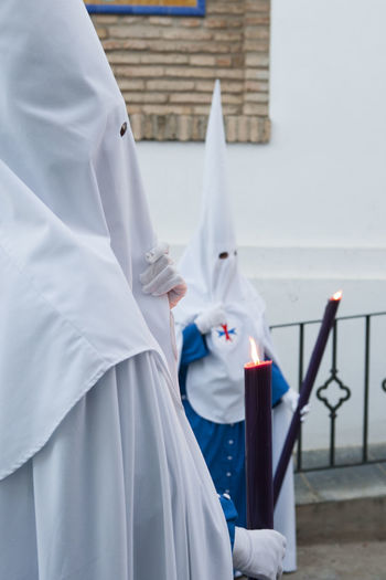 View of people wearing costume standing while holding candle