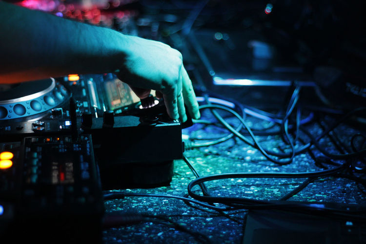 Cropped hand of man using sound mixer at night