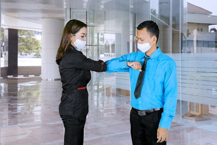 Businesswoman doing elbow bump with businessman while standing in building