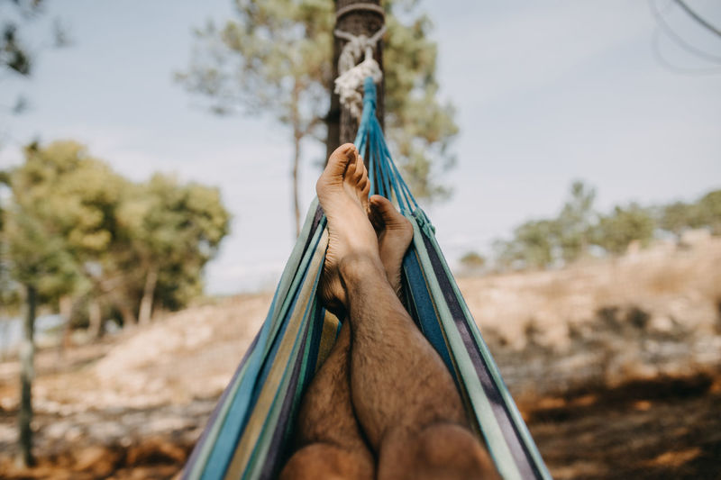 Low section of man hanging on rope against trees