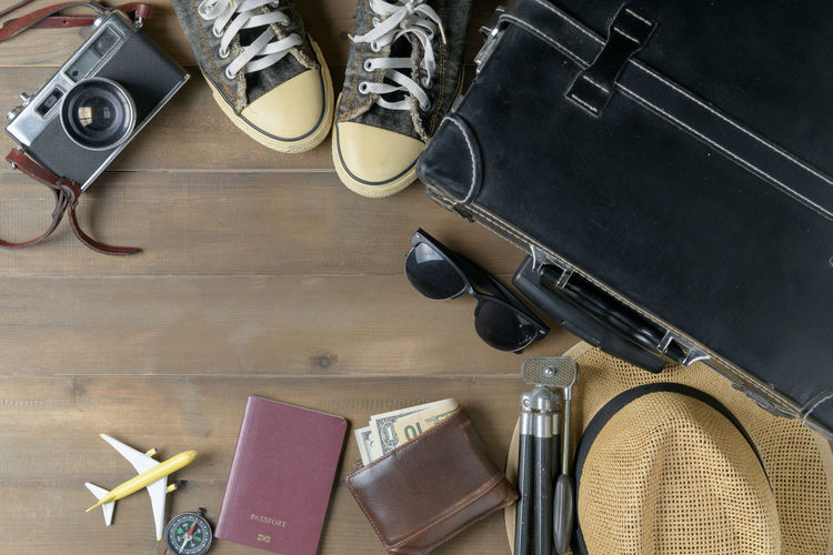 Directly above shot of travel equipment on wooden table