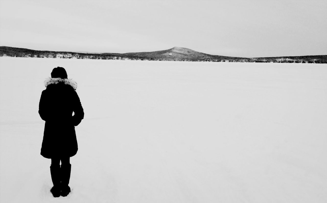 Full length rear view of woman standing on snow field