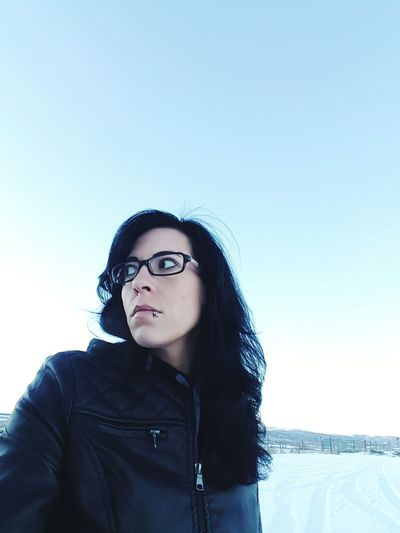 Close-up of woman wearing eyeglasses against sky
