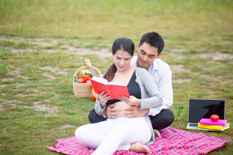 Young couple holding smart phone while sitting on grass