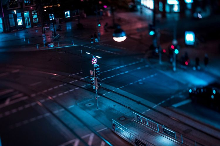 Tilt-shift image of illuminated street in city at night