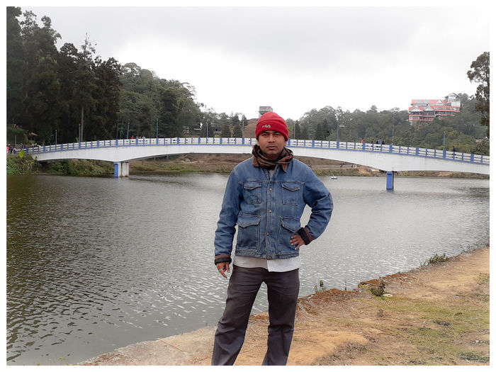Portrait of young man standing on bridge over river