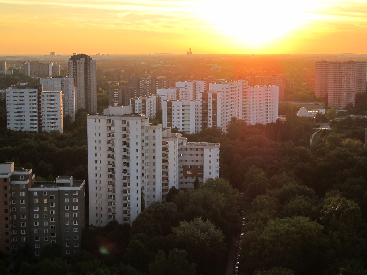 High angle view of cityscape and trees against sky during sunrise