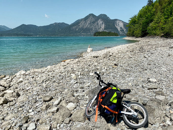 Bicycle and backpack on rocky beach by lake walchensee against mountains, bavaria, germany