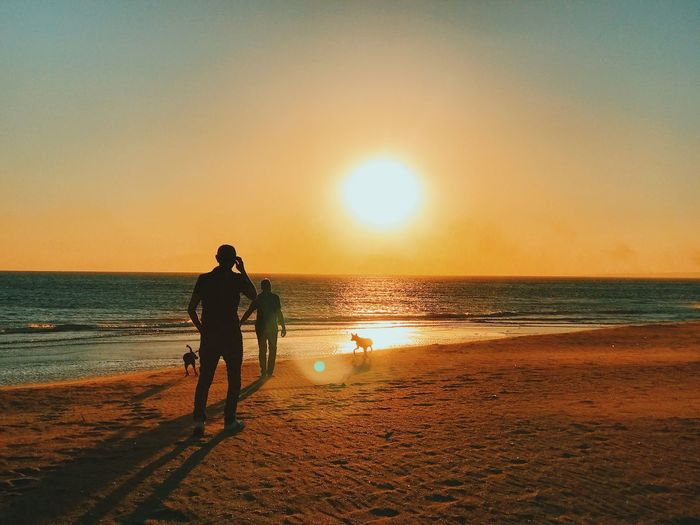 Radiating Adult Beach Beauty In Nature Full Length Horizon Over Water IPhoneography Leisure Activity Lifestyles Men Mobilephotography Nature Outdoors Real People Sand Scenics Sea Shore Silhouette Sky Standing Sun Sunset Togetherness Vacations Vscocam Water Wave Women