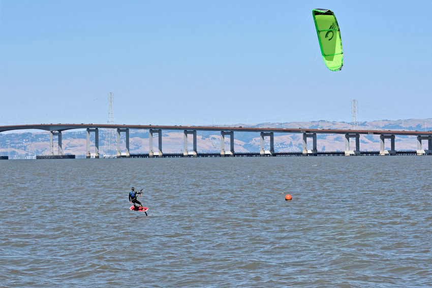 Kiteboarding In San Mateo 15 San Francisco Bay San Mateo Bridge Kiteboarder Kite Surfing Kiteboarding Wind Power Sail Power Colorful Sails Watersports Aquactic Sports Enjoying Life East Bay Hills Power Towers Power Lines Water Riding The Wind Course Marker Bridge Span Sports Photography
