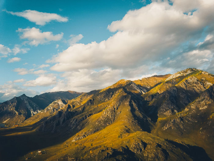 Bright yellow textured mountains against a blue sky, aerial view drone shot