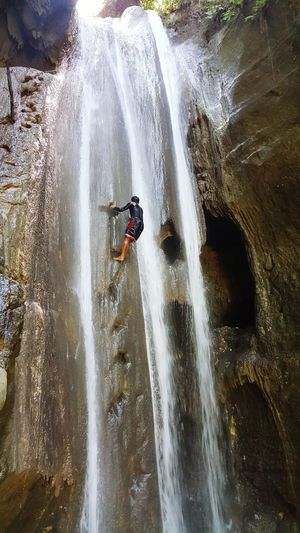 Full length of boy on rock at waterfall