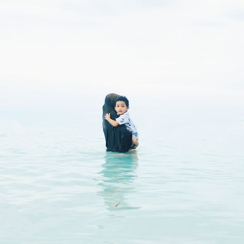 Side View Of Mother Carrying Son In Sea Against Clear Sky