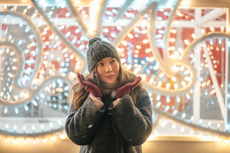 Christmas Christmas Decoration Portrait New Year Illuminated Warm Clothing Young Adult Front View Young Women Clothing One Person Winter Leisure Activity Women Standing Looking At Camera Real People Lifestyles Casual Clothing Happiness Adult Beautiful Woman Scarf Hairstyle